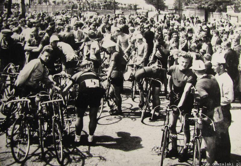 """Lata pięćdziesiąte XX wieku - kolarze czekają na start do wyścigu przed portiernią główną ZM """"Ursus"""" na ul. Traktorzystów. W głębi widać stację kolejową Ursus."""